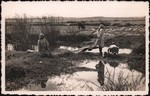 Front: Women doing washing at a small rive...